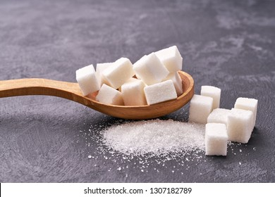 white sugar cubes in wood spoon on black table,selective focus