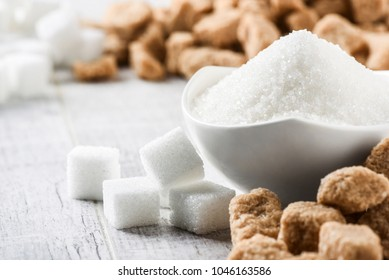 White sugar in glass bowl, Brown sugar in bacground. Sugar cubes