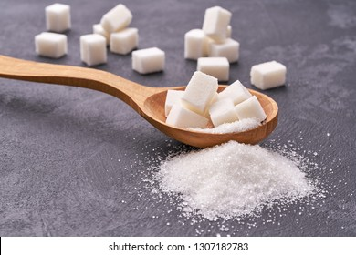 white sugar in wood spoon on black table,selective focus