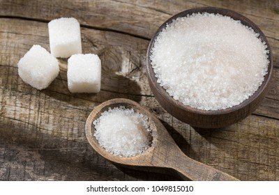 White sugar in wooden bowl and spoon - cubes