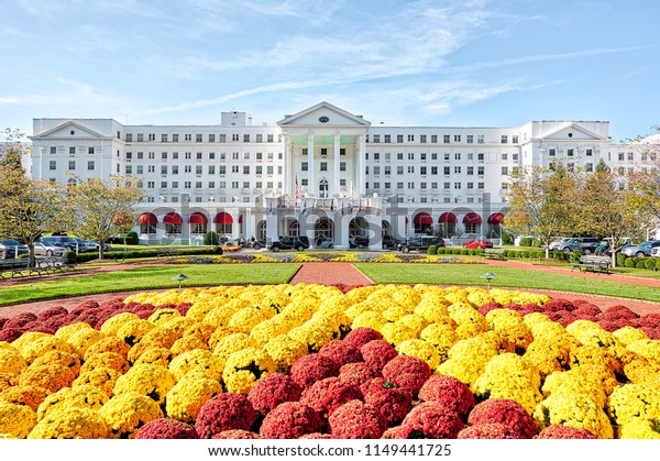 White Sulphur Springs, USA - October 20, 2017: Greenbrier Hotel resort exterior entrance with landscaped flowers, lawn, parked cars, in West Virginia
