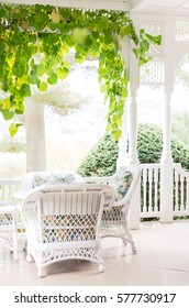 White summer covered porch with wicker furniture and hanging vines. Nostalgic pale background with selective focus
