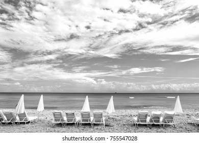White summer deck chairs and closed umbrellas standing in line on empty ocean coast with sand and cloudy blue sky in South Beach, Miami, Florida
