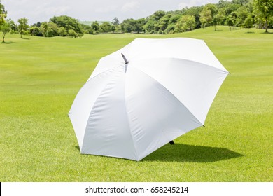 The white sun umbrella place on green grass golf course using for sun protection.