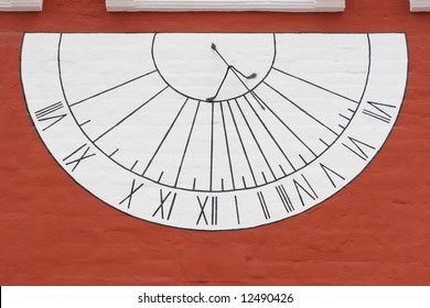 White sun-dial on red wall in Novodevichy Convent, Moscow, Russia