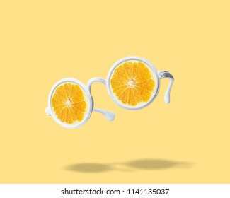 White sunglasses with orange on bright background. Summer minimal concept.