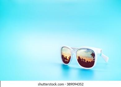 51a478123b White Sunglasses reflection sunset at palm tree landscape scene in light  blue studio