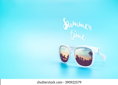 White Sunglasses reflection sunset at palm tree landscape scene in light blue studio,Summer Time concept,Leave space for adding your content or text