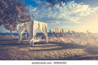 White sunlounger on greek coastline at sunrise