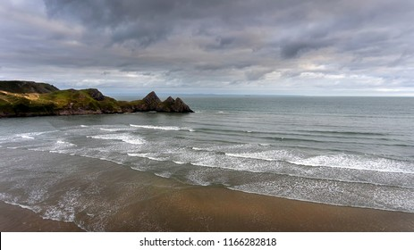 White surf and clouds at Three Cliffs Bay South Wales The beach at the dramatic Three Cliffs Bay on the Gower peninsula, Swansea, South Wales, UK