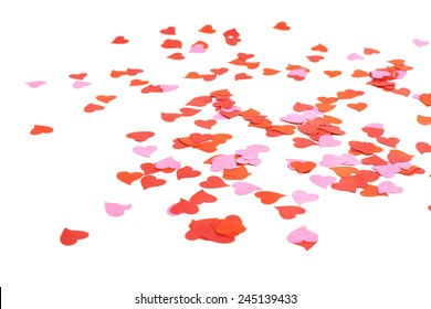 White surface covered with multiple red and pink heart shaped paper confetti as a romantic background composition