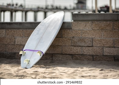 White surfboard leaning on the stone wall on the beach