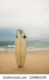 White Surfboard on sandy beach