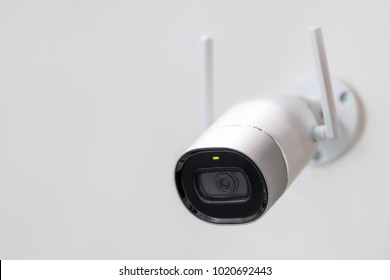 White surveillance camera. CCTV mounted on wall. Wifi wireless antennas enabled. Big brother watching you concept