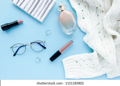 White sweater, glasses, notepad, women cosmetics and accessories on a blue pastel background