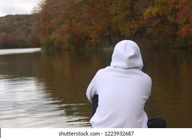 white sweatshirt looking over lake
