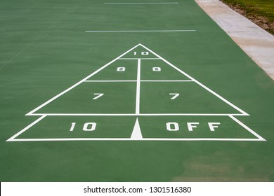 white symbol and numbers for green shuffleboard game on painted pavement