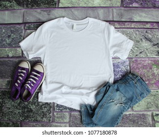 White T Shirt mockup flat lay on purple brick background with purple shoes and ripped jeans