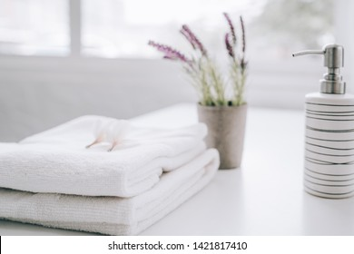 White table, body care products and towel. Bath preparation. White interior of bathroom.