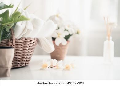 Weißer Tisch, Körperpflegeprodukte und Handtuch. Badezubereitung. Weiße Inneneinrichtung des Badezimmers