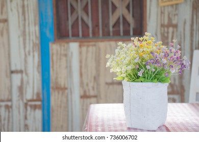 White table and chair flower vase in a restaurant old wooden floor. vintage style. Bright air.