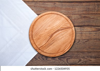 White Table cloth and pizza board on vintage wooden table. Top view mock up
