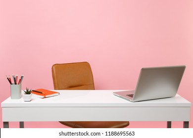 White table, desk with contempopary pc laptop notebook, pencils, Brown leather office chair. Workplace at office isolated on pastel pink background. Office accessories. Copy space for advertisement