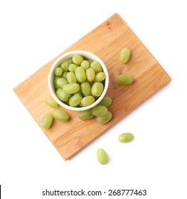 White table grapes in a ceramic bowl over the serving wooden board, composition isolated over the white background