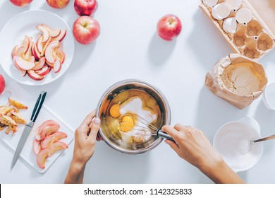 White table with ingredients for dough, cut and whole fruit. In the center female hands whisk sugar and raw eggs to make batter. Process of cooking apple pie, top view.