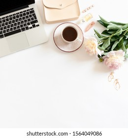 White table with laptop, mug of coffee, pink peonies and women's accessories