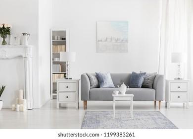 Table blanche sur moquette devant banquette grise à l'intérieur de l'appartement avec peinture et lampe. Photo réelle