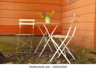 white table and outdoor chairs in an outdoor cafe