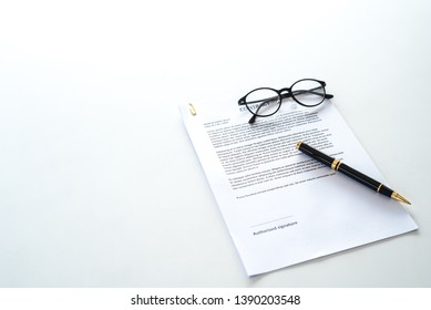 White table with paper contract detail and empty space to sign authorized signature, props with glasses and ink pen, copy space on the left