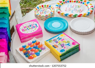 White table served with disposable tableware, colorful napkins and paper plates, ready for birthday party. Close up.