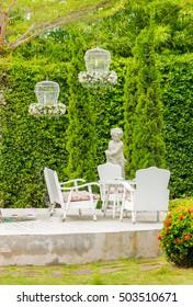 White table set and flower pot on relaxing space in cozy garden on summer./ Relaxing space in cozy garden.