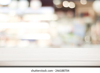 White table surface at cafe background for food and product display, Wood shelf for shop presentation background, Empty white wood table top, counter over blur bokeh light, retail store banner