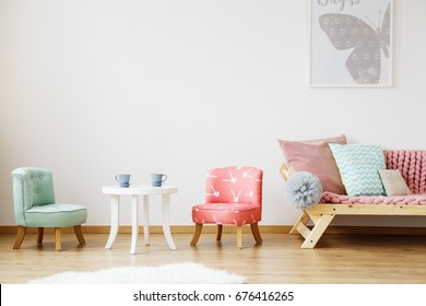 White table with tea cups and chairs for children in baby room with poster on the wall