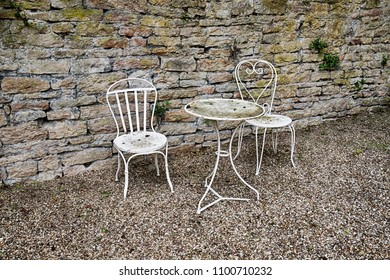 A white table and two chairs form a nice quiet area in a small garden court in the town of Beaune in the Burgundy region of France.