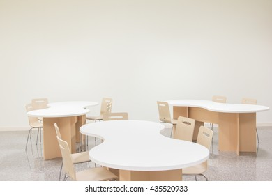 White table and wood chair in white room.