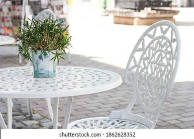 white table and wrought iron chair at a street cafe