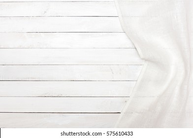 White tablecloth on a white wooden kitchen table. View from above with copy space.