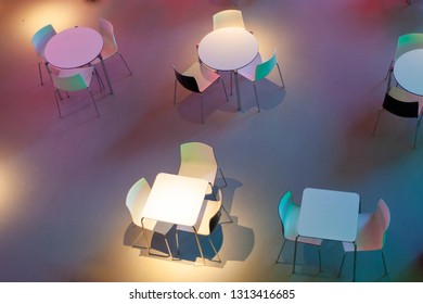 White tables and chairs in the cafe in the museum in the dark and light of different colors. View from the top.