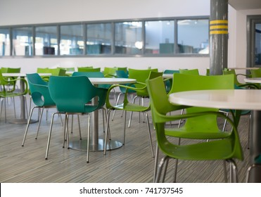 White tables green chairs in large canteen or meeting area in school college or work place.
