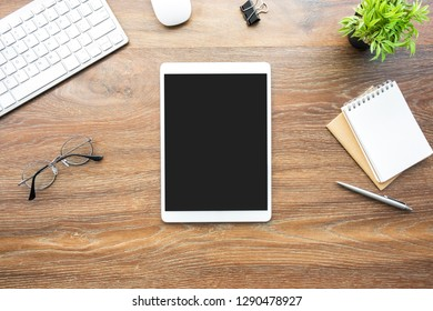 White tablet with black blank screen is on top of wood desk table with blank notebook and supplies. Top view, flat lay.