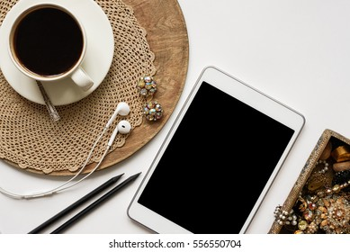 White tablet with blank copy space screen, cup of coffee, headphones, vintage jewerly on white background. Empty space for promotional content, for social media blogger, other app design. Flat lay.