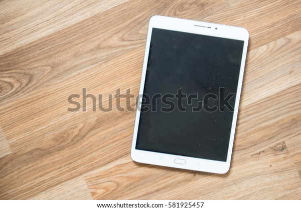 White Tablet with Blank Screen on Wood Background