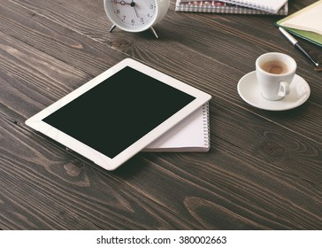 white tablet computer with blank screen where you can place your text on a dark wooden table in the morning