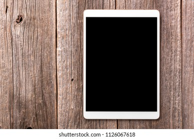 White tablet computer on old wood table background.