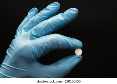 White tablet in a hand in a blue glove on a black background, concept.