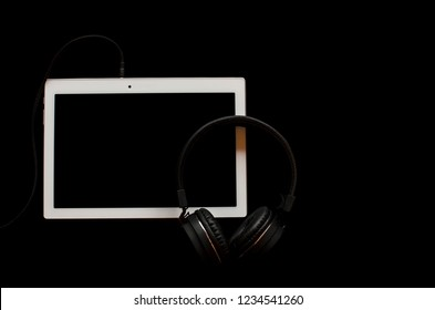 White tablet with headphones isolated on a black background